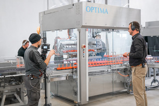 Optima Consumer project manager Jochen Weller (to the right of the picture) communicates with the customer and explains the processes going on inside the machine